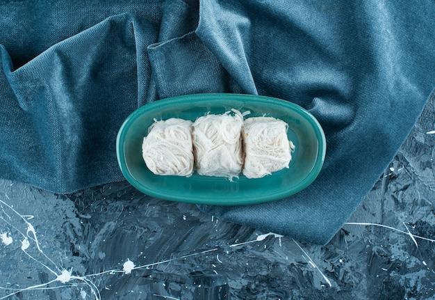 Traditionelle türkische zuckerwatte auf einem teller auf einem handtuch auf dem blauen tisch.