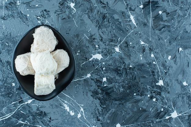 Traditionelle türkische zuckerwatte in einer schüssel auf dem blauen tisch.