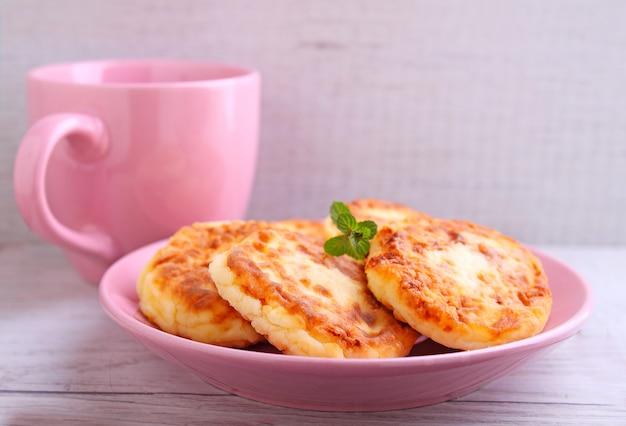 Traditionelle ukrainische und russische küche aus syrniki (hüttenkäsepfannkuchen, stückchen von hüttenkäse).