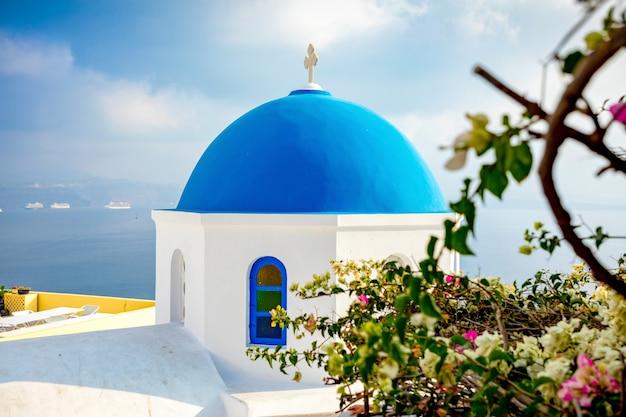 Traditionelle und berühmte häuser und kirchen mit blauen hauben in oia, santorini, griechenland