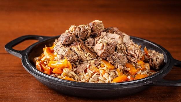 Traditionelle usbekische orientalische küche, pilaw oder plov mit großen stücken lammfleisch und karotten, gekocht in einer schwarzen gusseisernen pfanne aus kasan.