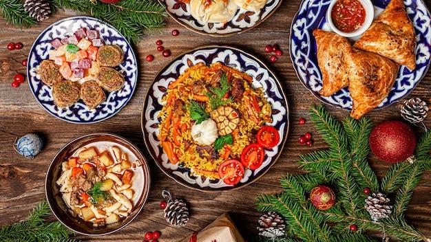 Traditionelle usbekische orientalische küche. usbekischer familientisch aus verschiedenen gerichten für die neujahrsfeiertage. das hintergrundbild ist eine draufsicht