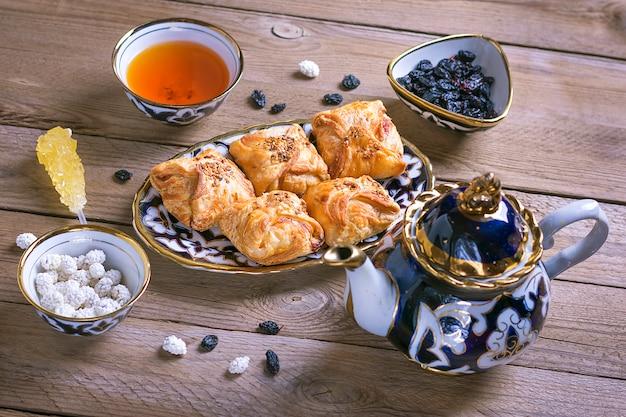 Traditionelle usbekische süßigkeiten - getrocknete aprikose, rohat turkish delight, rosine, samsa, mandel, teekanne und schüssel