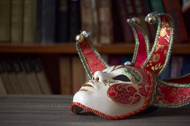 Traditionelle venezianische karnevalsmaske mit reichem dekor auf einem holztisch in der bibliothek, selektiver fokus