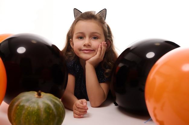 Traditionelle veranstaltung, halloween-party-konzept. schönes kleines hexenmädchen im reifen mit katzenohren, die auf weißem hintergrund mit kopienraum neben kürbis und orange schwarzen luftballons liegen