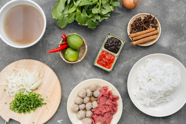 Traditionelle vietnamesische nudelsuppen pho in schalen, konkreter hintergrund. vietnamesische rindfleischsuppe pho bo, nahaufnahme. asiatisches/vietnamesisches essen. vietnamesisches abendessen. pho-bo-mahlzeit. ansicht von oben. gesund