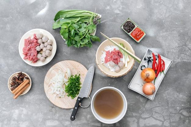 Traditionelle vietnamesische suppe pho bo mit kräutern, fleisch, reisnudeln, brühe. pho bo in schüssel mit stäbchen, löffel. platz für text. ansicht von oben. asiatische suppe pho bo auf holztischhintergrund. vietnamesische suppe
