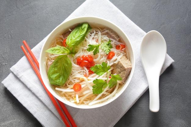 Traditionelle vietnamesische suppe pho bo mit kräutern, rindfleisch, reisnudeln, chili und sojasprossen.
