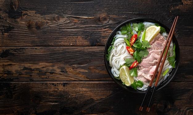 Traditionelle vietnamesische suppe pho bo mit rindfleisch und nudeln auf holzhintergrund draufsicht kopie raum copy