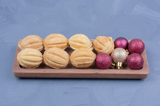 Traditionelle walnussplätzchen in einer hölzernen platte mit weihnachtsdekoration
