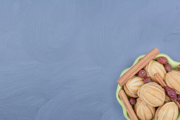Traditionelle walnussplätzchen mit zimtstangen und trockenen hüften in einer grünen tasse
