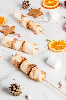 Traditionelle weihnachtsbonbons - zuckerstange, eibisch, getrocknete orange, lebkuchensterne, gebacken auf feuereibischaufsteckspindeln