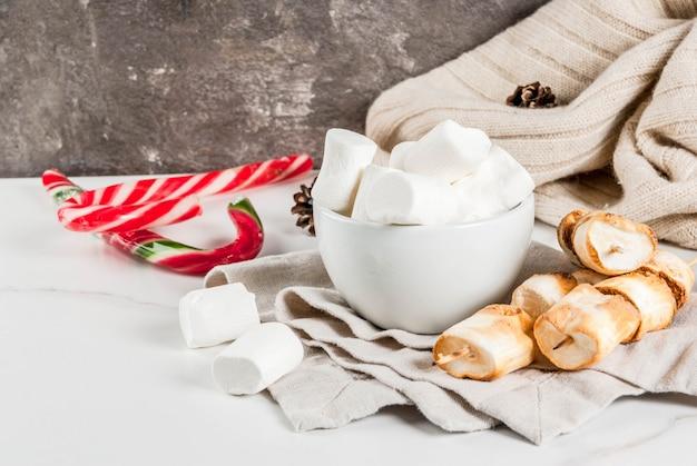 Traditionelle weihnachtsbonbons - zuckerstange, eibisch und auf feuer gebackene eibischaufsteckspindeln auf weißer szene