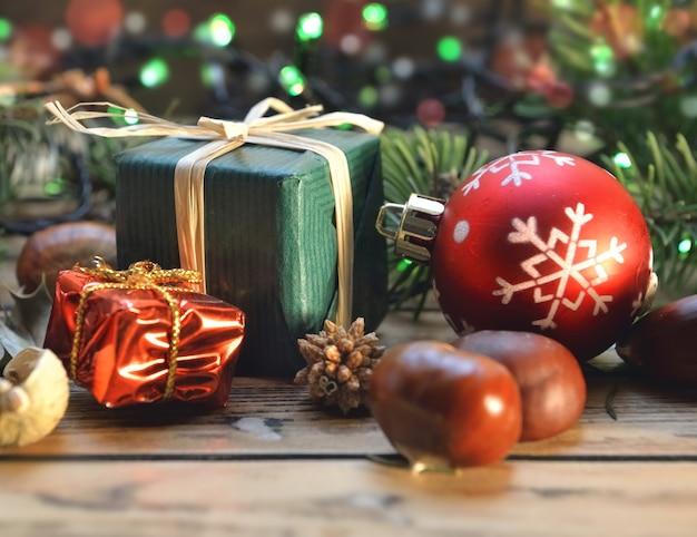 Traditionelle weihnachtsdekoration auf holztisch mit geschenkbox und lichtern
