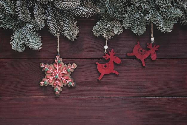 Traditionelle weihnachtsdekoration mit fichtenzweigen, hirschen und schneeflockenspielzeug