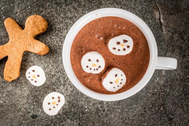 Traditionelle weihnachtsgetränkidee. tasse der heißen schokolade mit dem eibisch, verziert in form von schneemännern, auf schwarzer steintischplatteansicht