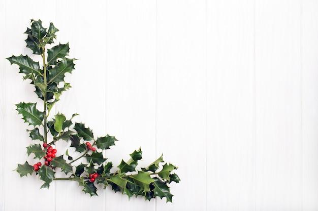 Traditionelle weihnachtsstechpalme mit roten beeren auf weißem holz