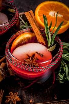 Traditionelle winter- und herbstgetränke. weihnachts- und thanksgiving-cocktails. glühwein mit orange, apfel, rosmarin, zimt und gewürzen auf einem dunklen steinhintergrund, draufsicht des kopienraumes