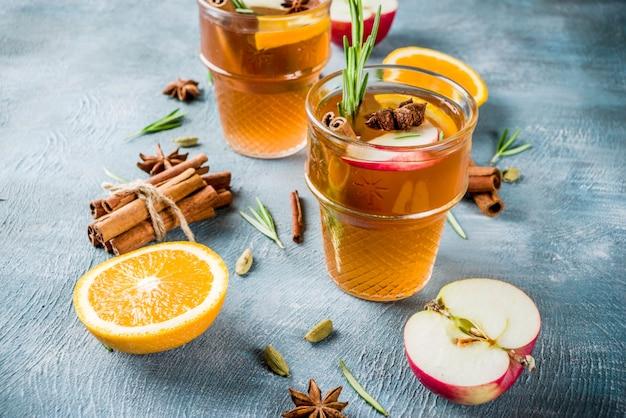 Traditionelle wintergetränke, glühweincocktail mit weißwein, mit gewürzen, apfel, orange