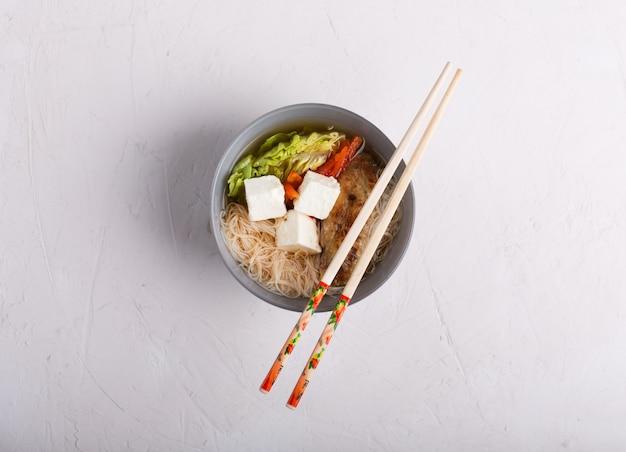 Traditionelle würzige asiatische suppe mit tofukäse und nudeln. weißer hintergrund