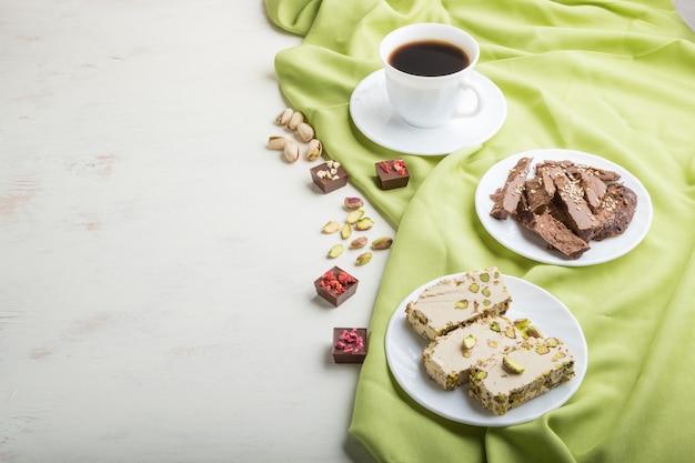 Traditioneller arabischer bonbonsesam halva mit schokolade und pistazie und einem tasse kaffee. seitenansicht
