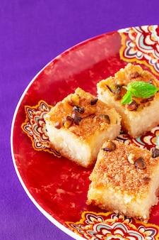 Traditioneller arabischer grießkuchen basbousa oder namoora mit nüssen, kokosnuss und orangenblütenwasser. speicherplatz kopieren. nahansicht. selektiver fokus.
