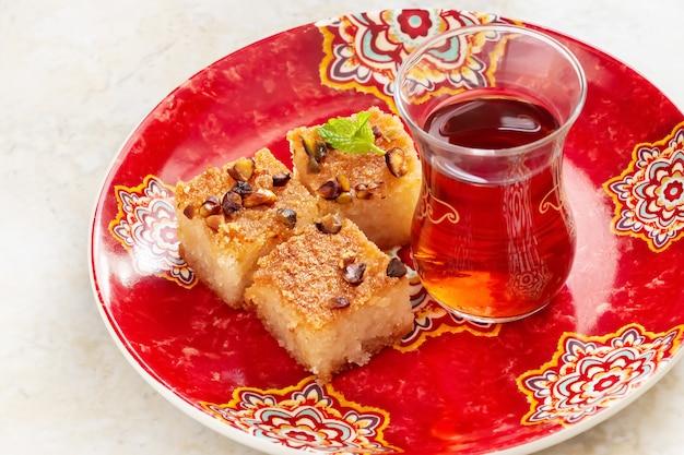 Traditioneller arabischer grießkuchen basbousa oder namoora mit nüssen und kokosnuss. nahansicht. selektiver fokus. draufsicht.