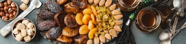Traditioneller arabischer tee und trockene früchte und nüsse, flach gelegt