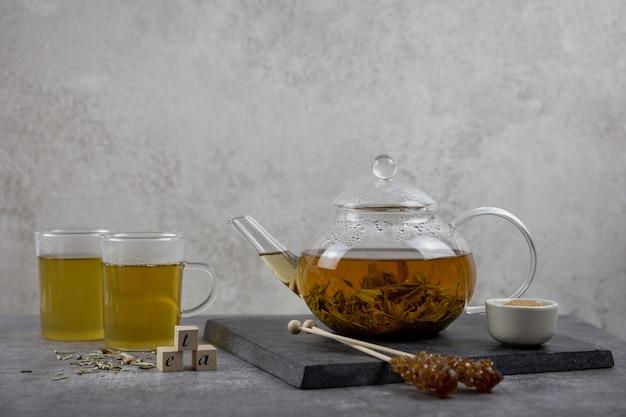 Traditioneller asiatischer grüner tee in einer glasteekanne. heißes gesundes getränk auf dunklem hintergrund.