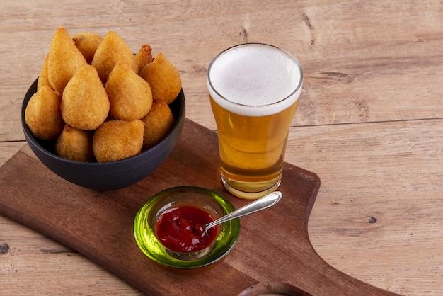 Traditioneller brasilianischer gebratener chiken-snack und ein glas bier