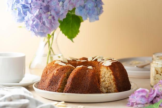 Traditioneller bundt-kuchen, hausgemachter gebäck gebackener runder kuchen mit kaffeetasse und blumen im hintergrund. schritt für schritt rezept.