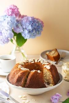 Traditioneller bundt-kuchen, hausgemachter gebäck gebackener runder kuchen mit kaffeetasse und blumen im hintergrund