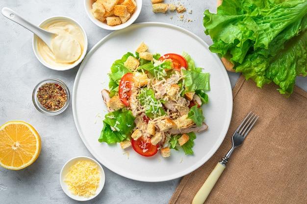 Traditioneller caesar-salat mit croutons und frischem gemüse auf einer grauen schreibtischoberansicht horizontal