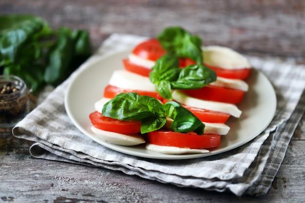 Traditioneller caprese-salat mit tomaten-mozzarella und basilikum.