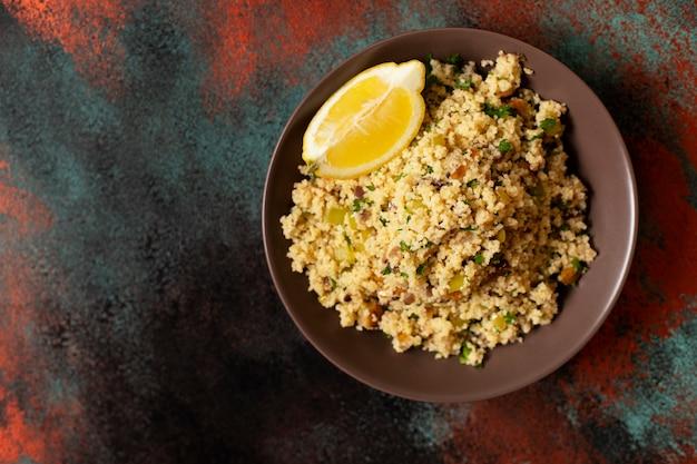Traditioneller couscous mit gemüse und kräutern in einer schüssel. levantinischer vegetarischer salat. libanesische, arabische küche. draufsicht. speicherplatz kopieren