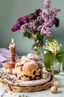 Traditioneller cupcake-osterkuchen-kraffin mit rosinen und puderzucker auf dem tisch. osterkuchen, kerzen und ein strauß lila blumen.