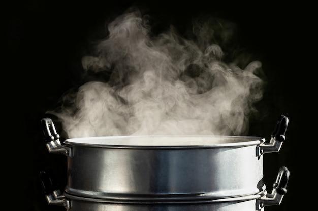 Traditioneller dampftopf mit weißem rauch beim kochen