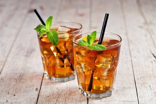 Traditioneller eistee mit zitrone, tadellosen blättern und eiswürfeln in zwei gläsern auf rustikalem holztisch.