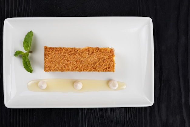 Traditioneller esterhazy-kuchen mit minze auf schwarzem holzhintergrund