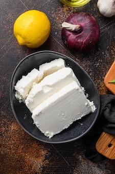 Traditioneller feta-käse in der schwarzen schüssel, draufsicht.