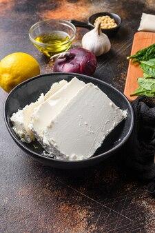 Traditioneller feta-käse in der schwarzen schüssel, seitenansicht.