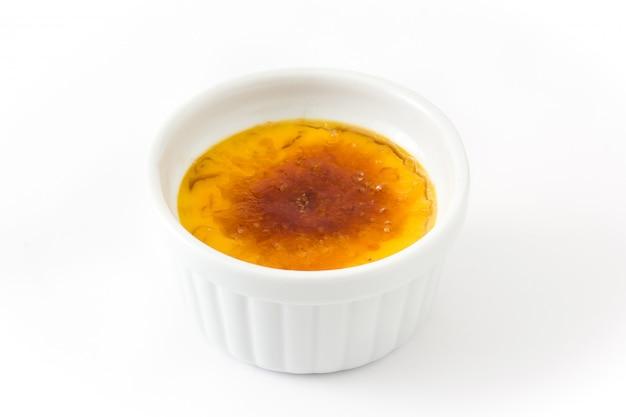 Traditioneller französischer creme brulee nachtisch mit dem karamellisierten zucker getrennt auf weiß.