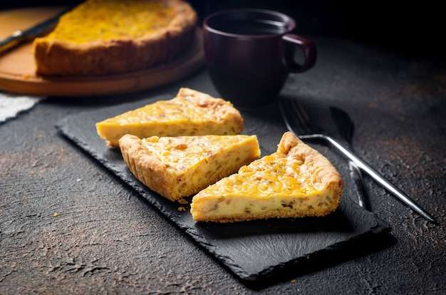 Traditioneller französischer hausgemachter zwiebelkuchen oder quiche. offener kuchen mit käse und zwiebeln auf rundem brett.