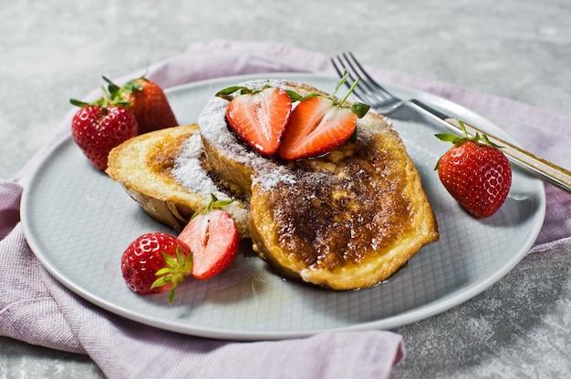 Traditioneller französischer toast mit erdbeeren an.