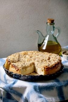 Traditioneller gebackener brotkuchen mit zwiebeln, kräutern und käse in keramikschale, serviert auf blau-weißer tischdecke