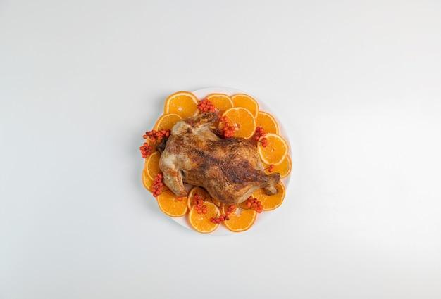 Traditioneller gebratener truthahn zu weihnachten oder thanksgiving, garniert mit orangefarbenen fruchtscheiben und vogelbeeren isoliert auf weißem hintergrund