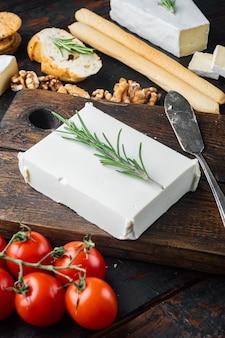 Traditioneller griechischer feta-käse-satz, auf dunklem hölzernem hintergrund