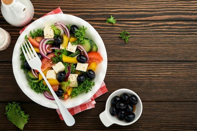 Traditioneller griechischer salat aus frischen gurken, tomaten, paprika, salat, roten zwiebeln, feta-käse und oliven mit olivenöl auf weißem teller. gesundes essen, ansicht von oben.