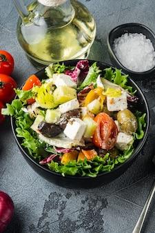 Traditioneller griechischer salat mit frischem gemüse, feta und oliven, auf grauem tisch, draufsicht flach gelegt