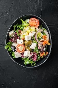Traditioneller griechischer salat mit frischem gemüse, feta und oliven auf schwarz